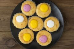 Muffins with pink and yellow cream, on rustic background. Black plate. Top view royalty free stock photos