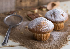 Muffins powdered by sugar on jute and white wooden background. Royalty Free Stock Photos