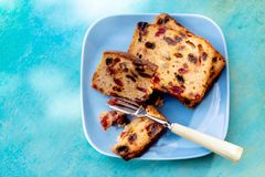 Muffins with raisins on a rustic wooden table. Fruitcake or slices cupcake on a blue plate. stock images