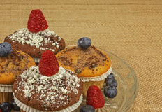 Muffins with raspberries and blueberries. Four muffins sprinkled with grated chocolate and garnished with fresh raspberries and blueberries on a glass plate and Stock Photo