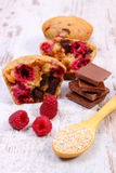 Muffins with raspberries, chocolate and oat bran on spoon, wooden background, delicious dessert. Homemade fresh baked muffins with raspberries, pieces of Stock Photo