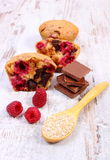 Muffins with raspberries, chocolate and oat bran on spoon, wooden background, delicious dessert Royalty Free Stock Photos