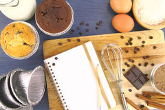 Muffins recipe. Recipe book and muffins on the table Royalty Free Stock Photo