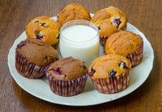 Muffins rond een glas melk op een witte plaat Stock Afbeeldingen