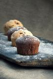 Muffins on rustic bakery peel. Four chocolate and vanilla muffin on rustic bakery peel with sugar powder Stock Images