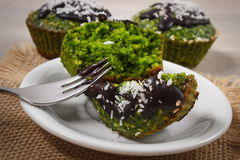 Muffins with spinach, desiccated coconut and chocolate glaze, delicious healthy dessert Stock Image