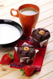 Muffins and strawberries for breakfast. Black cup filled with milk chocolate muffins, strawberries and cup of espresso on pine wood Stock Photo