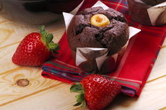 Muffins and strawberries for breakfast. Chocolate muffins, strawberries closeup on pine wood Royalty Free Stock Images