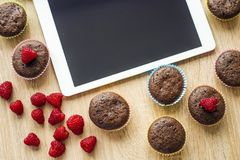 Muffins and tablet on the table Stock Photography