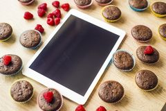 Muffins and tablet on the table Stock Image