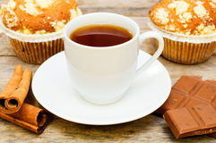 Muffins with tea, cinnamon sticks and chocolate Royalty Free Stock Image