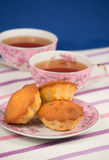 Muffins and tea. Three muffins on a saucer and tea royalty free stock photos
