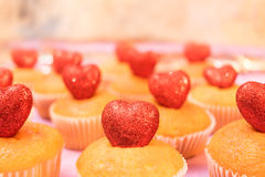 Muffins top view with sparkling red hearts side view toned selective focus Stock Image