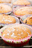 Muffins topped with powdery sugar on a wooden background Royalty Free Stock Photography
