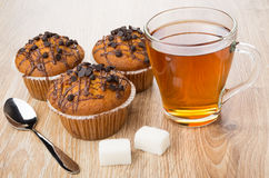 Muffins, transparent cup of tea, lumpy sugar and spoon Stock Photos