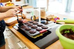 Muffins uit de oven worden genomen die stock fotografie