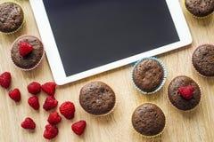 Muffins und Tablette auf dem Tisch Stockfotografie