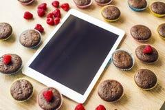 Muffins und Tablette auf dem Tisch Stockbild