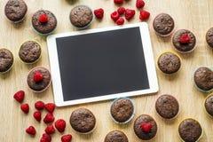 Muffins und Tablette auf dem Tisch Lizenzfreies Stockbild
