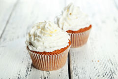 Muffins with white cream on wooden background Stock Photography