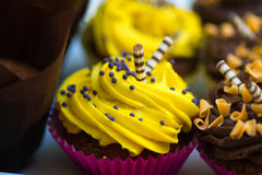 Muffins with yellow cream. And decorated with flakes royalty free stock images