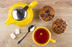 Muffins, yellow teapot, cup of tea, lumpy sugar and spoon Royalty Free Stock Images
