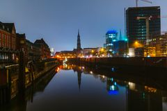 Evening and night sketches on the millet streets in the center of the port of Hamburg. The muffled light makes its way through an easy fog. Reflections of the Royalty Free Stock Photography