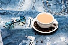 Mug вполне кофе с молоком и солнечными очками на джинсах, defocused принимать человека принципиальной схемы кофе пролома Чашка с  Стоковое Изображение