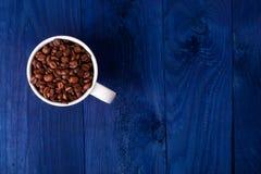 Mug вполне кофейных зерен на голубой деревянной предпосылке Стоковое Фото