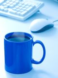Mug. Blue Mug of coffee or tea with computers mouse & keyboard in background. Light steam. Soft focus, blue duotone Stock Image