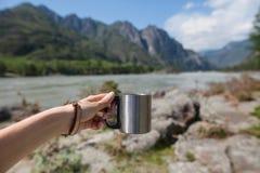 Mug on a background of mountains. Female hand holding a mug on a background of mountains and rivers royalty free stock photo