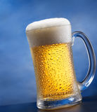 Mug of beer. Against blue background Stock Photos