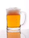 A mug of beer. With froth and slight spill stock image