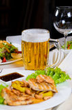 Mug of Beer Amidst Plated Dishes on Table Royalty Free Stock Images
