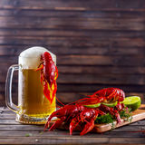 Mug of beer and boiled crawfish on a wooden table royalty free stock photo
