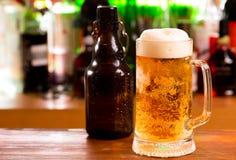 Mug of beer and bottle Stock Image
