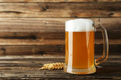Mug of beer on a brown wooden background. Royalty Free Stock Photography