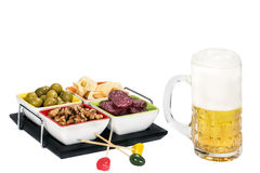 Mug of beer with cheese, olives , salami and nuts. On a white background Royalty Free Stock Image