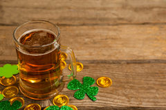 Mug of beer, chocolate gold coins and shamrock for St Patricks Day. On wooden table Royalty Free Stock Photo