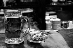 Mug of beer, cigarette and ashtray Royalty Free Stock Photography