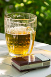 Mug of beer and cigarettes summer day on nature Royalty Free Stock Photo