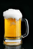 Mug of beer with froth. Over black background stock photography