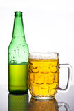 Mug of beer. A mug of beer with green bottle behind Royalty Free Stock Images