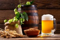Mug of beer with green hops, wheat ears and wooden barrel. On wooden background royalty free stock photos