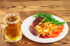 Mug of beer and grilled sausages with fried potatoes, sliced tomatoes, fresh produce, ketchup in plate on wooden table Stock Images