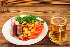 Mug of beer and grilled sausages with fried potatoes, sliced tomatoes, fresh produce, ketchup in plate on wooden table Royalty Free Stock Photography