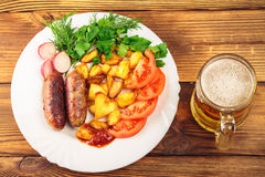 Mug of beer and grilled sausages with fried potatoes, sliced tomatoes, fresh produce, ketchup in plate on wooden table Royalty Free Stock Photos
