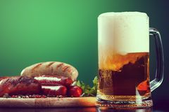 Mug of beer with grilled sausages on green background. Oktoberfest drink and food Royalty Free Stock Photo