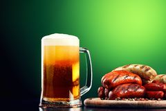 Mug of beer with grilled sausages on green background. Oktoberfest drink and food Stock Photography