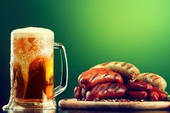 Mug of beer with grilled sausages on green background. Oktoberfest drink and food Royalty Free Stock Photography